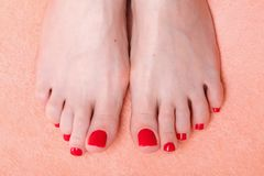 Woman feet with red toenails on towel Stock Images