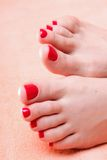 Woman feet with red toenails on towel Royalty Free Stock Photography