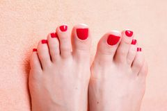 Woman feet with red toenails on towel Royalty Free Stock Images