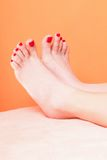 Woman feet with red toenails on towel Stock Photos