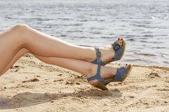 Woman feet in sandals on the beach Royalty Free Stock Image