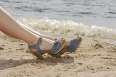 Woman feet in sandals on the beach Stock Photography