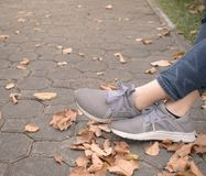 Woman feet in sneaker on green grass in the park stock images