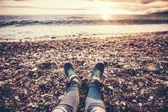 Woman Feet sneakers on beach sea sunset Stock Photos