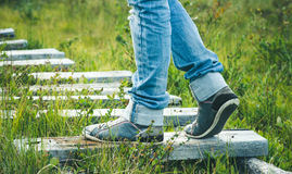 Woman Feet sneakers walking on wooden road Outdoor Royalty Free Stock Photos