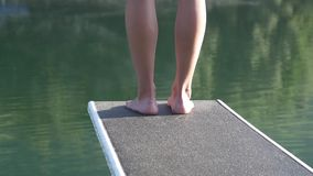 Woman feet on springboard in front of a lake. Female legs on springboard ready to jump into the water with reflection of landscape stock video footage
