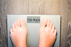 Woman feet stepping on a weight scale having problems with her diet Royalty Free Stock Image