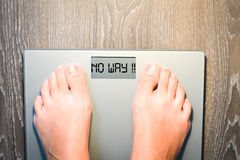 Woman feet stepping on a weight scale having problems with her diet Stock Photography
