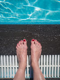 Woman feet at the swimming pool Stock Images