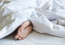 Woman feet under white blanket and bed sheet Stock Photography