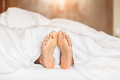 Woman feet under white blanket side view. Beautiful young woman feet with blue pedicure on the bed. Sleeping woman legs under the white blanket royalty free stock image