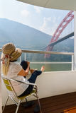 Woman with feet up on railing of Cruise ship China Royalty Free Stock Photography