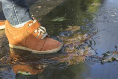 woman feet walking in a puddle in orange boots stock images
