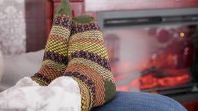Woman feet in warm woollen socks next to a burning fireplace stock video