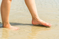 Woman feet in water on beach Royalty Free Stock Photos