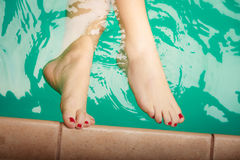 Woman feet in water at poolside. Woman feet in water at swimming pool poolside. Relax and leisure Royalty Free Stock Photo
