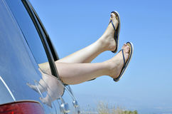 Woman with feet in the way the car window Stock Photos