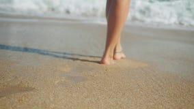 Woman feet wearing bracelet walking on tropical beach to the sea leaving footprints in sand in slow motion. 1920x1080. Woman feet walking on tropical beach stock footage
