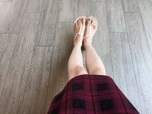 Woman feet wearing pink sandals and scot dress of fashion. Selfie of feet and legs in pink shoes  on wooden background. Great for any use Stock Photo