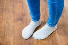 Woman feet wearing socks and jeans trousers. Woman feet wearing white socks and jeans trousers standing on wooden floor Stock Photos