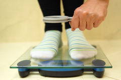 Woman feet on weighing scales looking weight over magnifying. Glass. exaggerate with weight loss concept Stock Photos