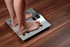 Woman feet on weight scale Royalty Free Stock Photography