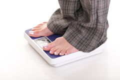 Woman feet and weight scale isolated on white Stock Photos