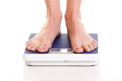 Woman feet and weight scale isolated on white background Stock Photos