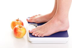 Woman feet and weight scale  on white background Stock Photo