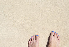 Woman feet on white beach sand. White sand top view photo for background. Sunny day by sea on exotic island concept. White sand texture with bare foot banner Royalty Free Stock Photo