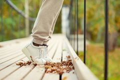 Woman feet in white shoes standing on autumn hanging bridge Stock Images