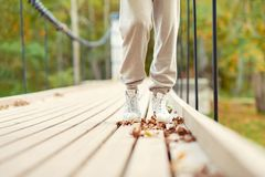 Woman feet in white shoes walking in autumn park. On hanging bridge. Front view. Outdoors Autumn season multicolored horizontal image Royalty Free Stock Photos