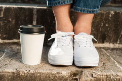 Woman feet in white sneakers standing near a coffee cup Stock Image