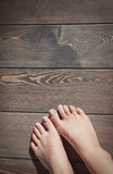 Woman feet on the wooden floor Royalty Free Stock Images
