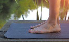 Woman feet on yoga mat before practicing. On pond Royalty Free Stock Photo