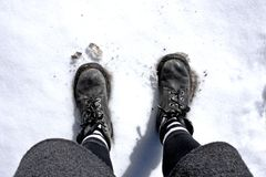 Woman feets on the snow with sunlight from high angle royalty free stock images