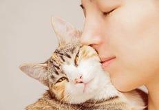 Woman and feline. Happy woman is hugging orange tabby feline stock photo