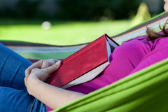 Woman fell asleep with book on hammock Royalty Free Stock Image