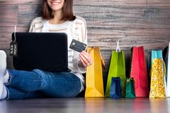 Woman female adult smiling buying making payment on fashion cloth internet online store shop by credit debit card with laptop stock photo