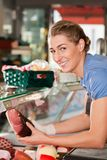 Woman or female butcher with raw ham in butchers shop Royalty Free Stock Image
