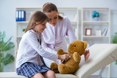 The woman female doctor examining little cute girl with toy bear royalty free stock photo