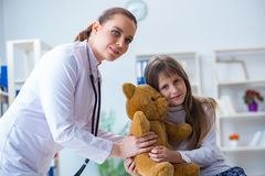 The woman female doctor examining little cute girl with toy bear royalty free stock photography