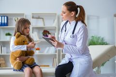 The woman female doctor examining little cute girl with toy bear royalty free stock images