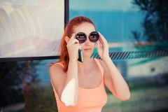 Woman female girl sitting in a bus station adjusting round sunglasses. Attractive trendy woman female girl sitting in a bus station adjusting round sunglasses royalty free stock photo