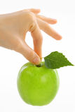 Woman, female hand take green apple with leaf Royalty Free Stock Photo