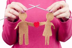 Woman female knits silhouette of woman and man in love. With red love shape by knitted needles. Relationship concept Royalty Free Stock Photo