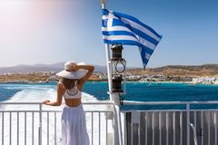 Woman on a ferry boat in the aegean sea, Greece. Woman in a white dress next to to a Greek flag on a ferry boat in the aegean sea, Greece stock photo