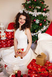 Woman in festive dress in front of Christmas tree Royalty Free Stock Images