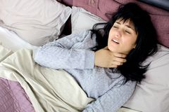 Woman with fever and throat problem in bed sick Royalty Free Stock Photos