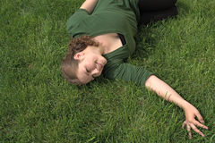 Woman on field. Young woman lying on green grass and smile Royalty Free Stock Images